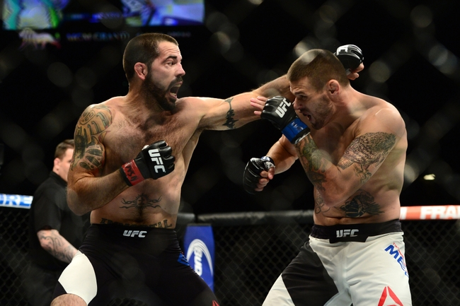 Jul 11, 2015; Las Vegas, NV, USA; Matt Brown (red gloves) and Tim Means (blue gloves) fight during UFC 189 at MGM Grand Garden Arena.  Brown won via first round submission. Mandatory Credit: Joe Camporeale-USA TODAY Sports